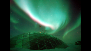 A picture of the aurora over top of a dome structure in the snow